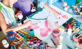 Group  of unrecognizable children painting pictures with watercolors working together in art studio painting picture for Mothers Day