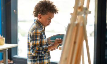 Clever schoolboy in casualwear standing in front of easel and painting picture at lesson